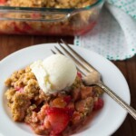 strawberry rhubarb crisp with oatmeal cookie streusel in white bowl with ice cream scoop and fork