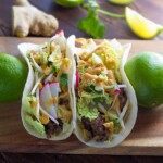 two ginger beef tacos with peanut sauce and trimmings