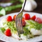 cilantro chile pesto fish on white plate with tomatoes and fork