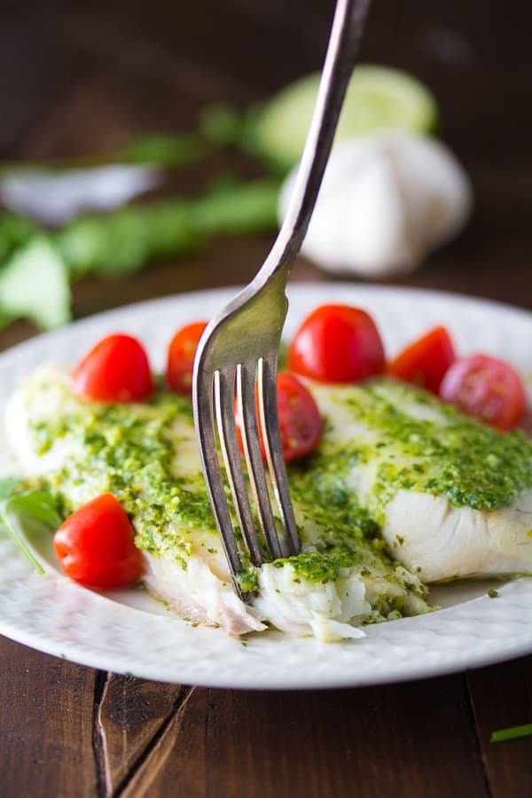 fork pressing into a cooked tilapia fillet spread with cilantro jalapeno pesto and tomatoes