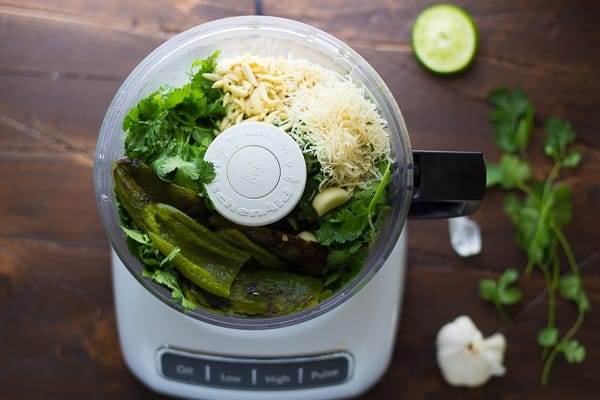 overhead view of the food processor containing the cilantro jalapeno pesto ingredients before blending