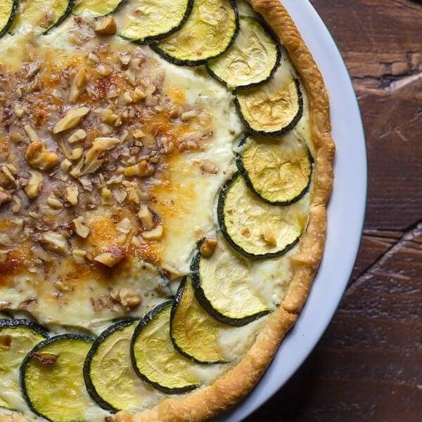 overhead shot of zucchini ricotta quiche with crumbled walnuts