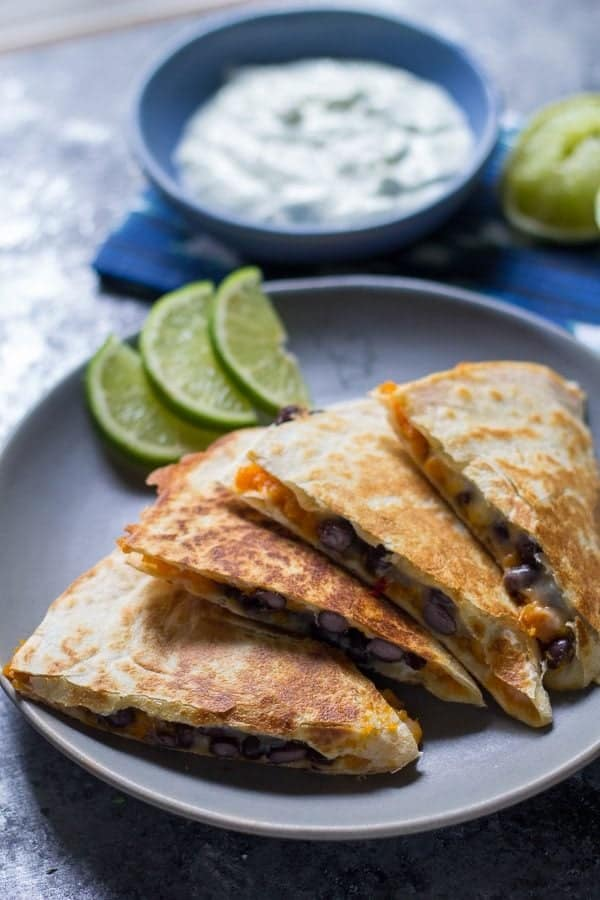 chipotle sweet potato black bean quesadillas on gray plate with lime slices