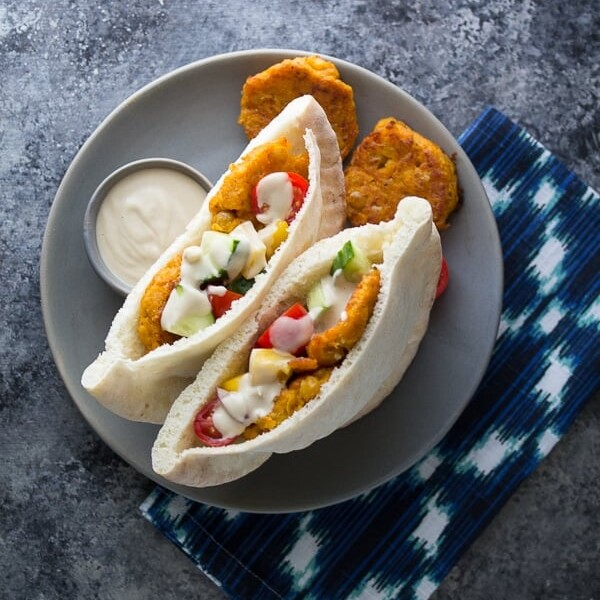 two sweet potato falafel pitas on gray plate with dipping sauce