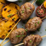 thai curry beef koftas with coconut sauce on gray plate with sweet potatoes and tomatoes