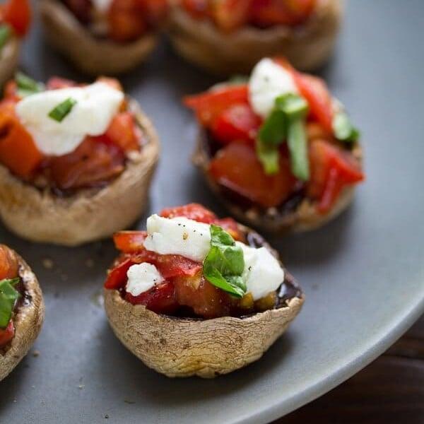 bruschetta and goat cheese stuffed mushroom caps on gray plate