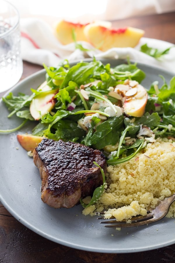 cooked lamb chop on plate with salad and couscous