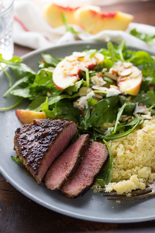 brown sugar chili lamb chops sliced open on plate with salad and couscous