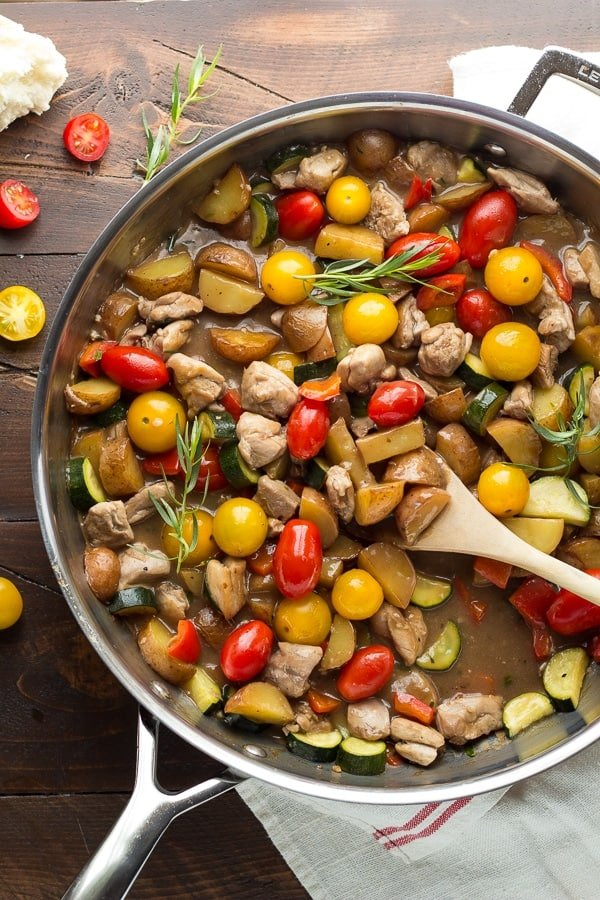 overhead view of skillet containing chicken, potatoes, herbs and tomatoes