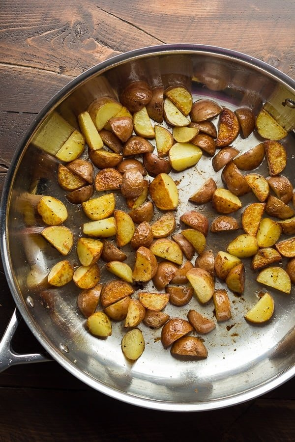 showing the process of browning the potatoes in the skillet