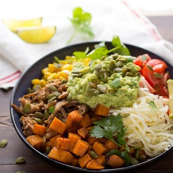 fall burrito bowl with maple pork sweet potatoes and pepitas in black bowl