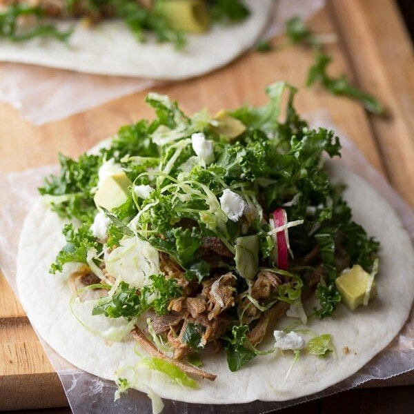 maple pork tacos with kale and brussels slaw on wood board