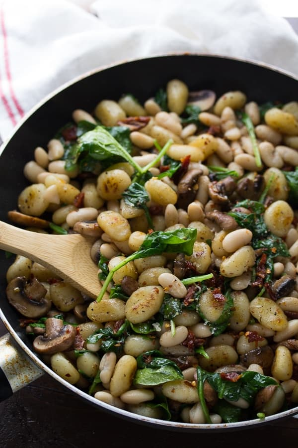 Gnocchi With Sundried Tomatoes, spinach, mushrooms and White Beans in large skillet
