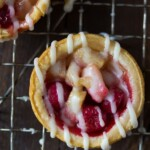 overhead shot of mini pear cranberry pie with brown butter glaze on wire rack