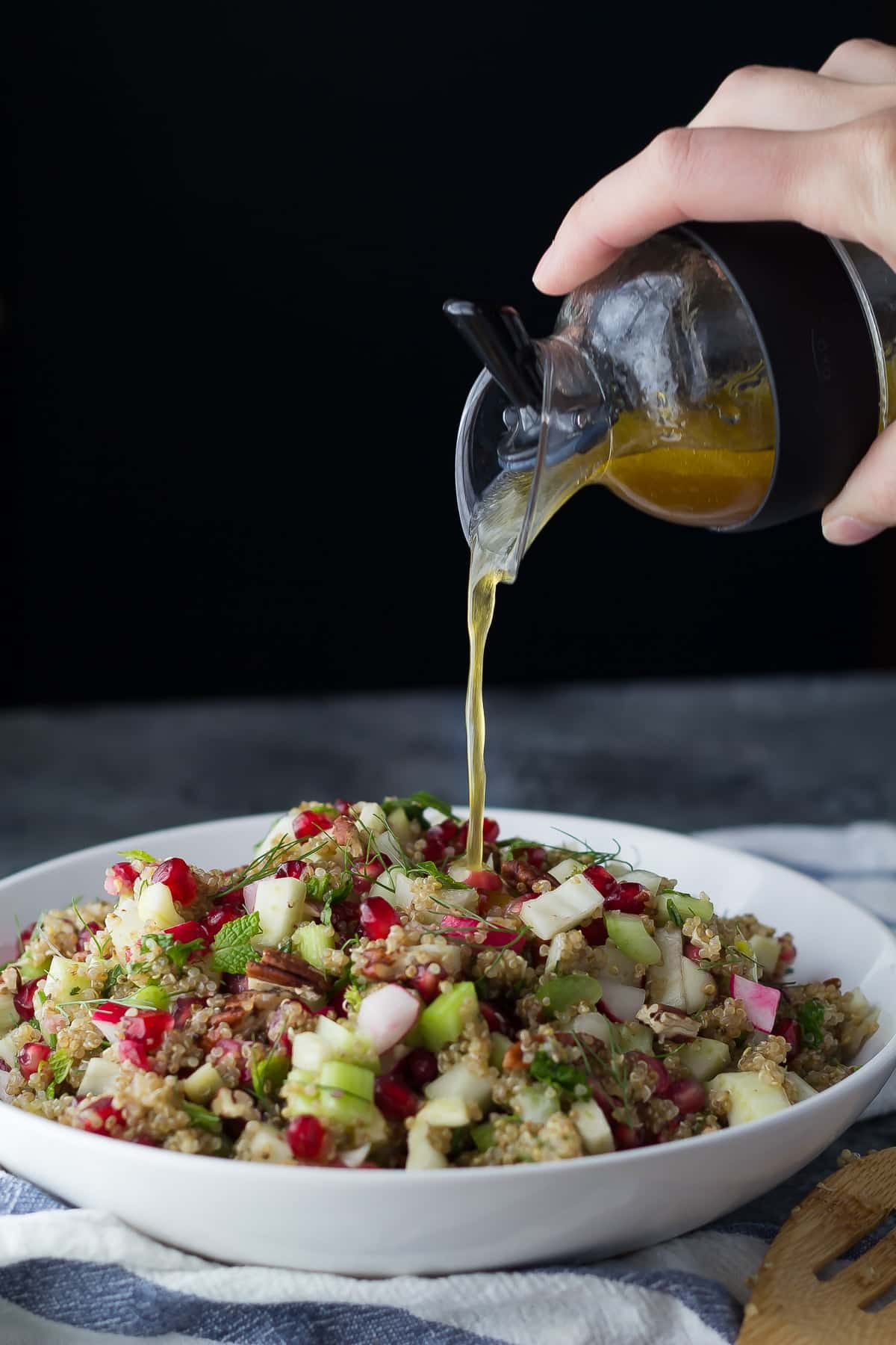 pouring vinaigrette over a bowl holding the fennel quinoa salad