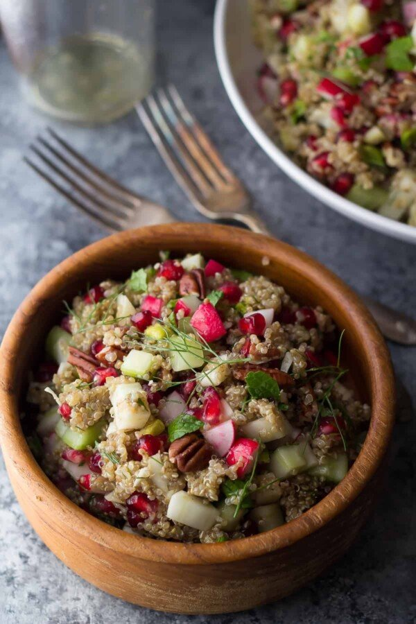 pomegranate fennel quinoa salad in wood bowl with forks