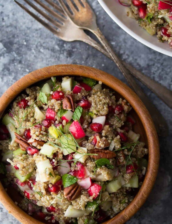 overhead shot of pomegranate fennel quinoa salad in wood bowl with forks