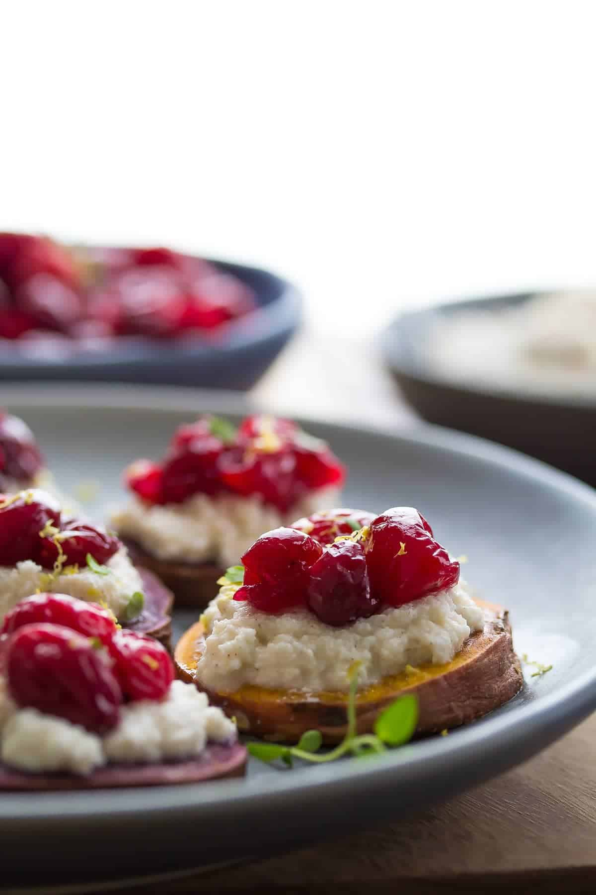 side angle of a sweet potato crostini topped with spiced ricotta and roasted cranberries