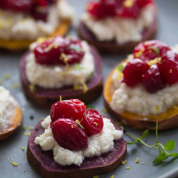 three sweet potato ricotta and cranberry rostinis on gray plate