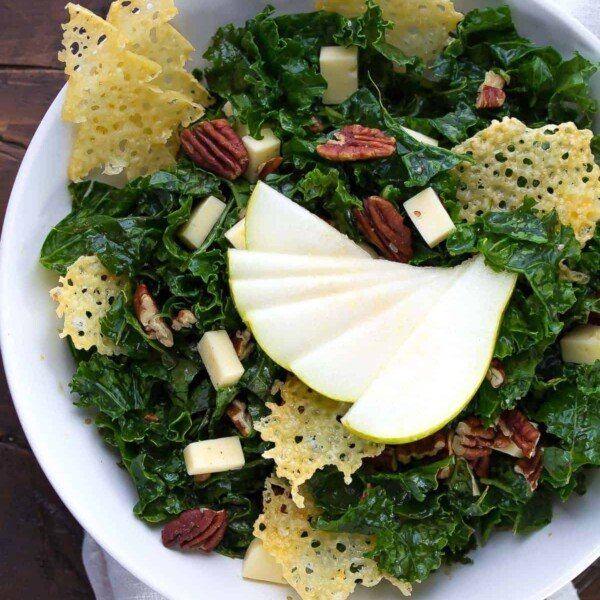 white bowl filled with balsamic winter kale salad and havarti crisps