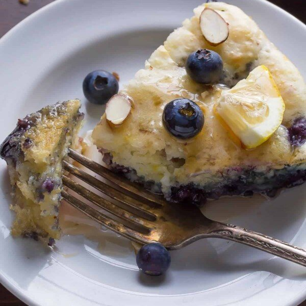 overhead shot of deep dish blueberry almond pancake on white plate with fork