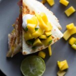 overhead shot of jamaican shrimp quesadillas with mango salsa on gray plate