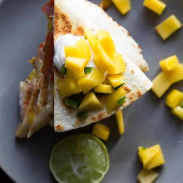 overhead shot of jamaican shrimp quesadillas with mango salsa on gray plate