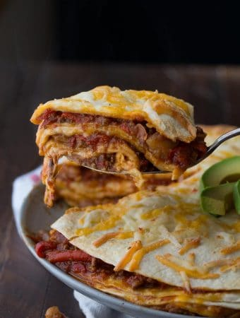 chili tortilla stacks on gray plate with avocado slices