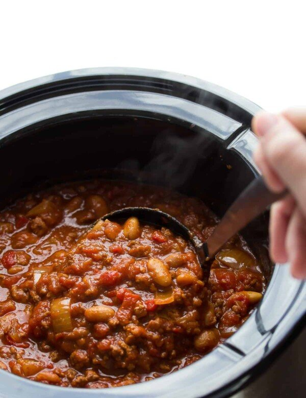 hand stirring roasted red pepper chili in the crock pot