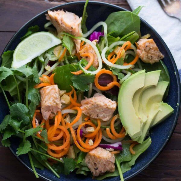 overhead shot of asian salmon salad with candied ginger and lime vinaigrette in navy blue bowl
