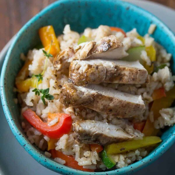 overhead shot of jerk chicken coconut rice with vegetables in blue bowl