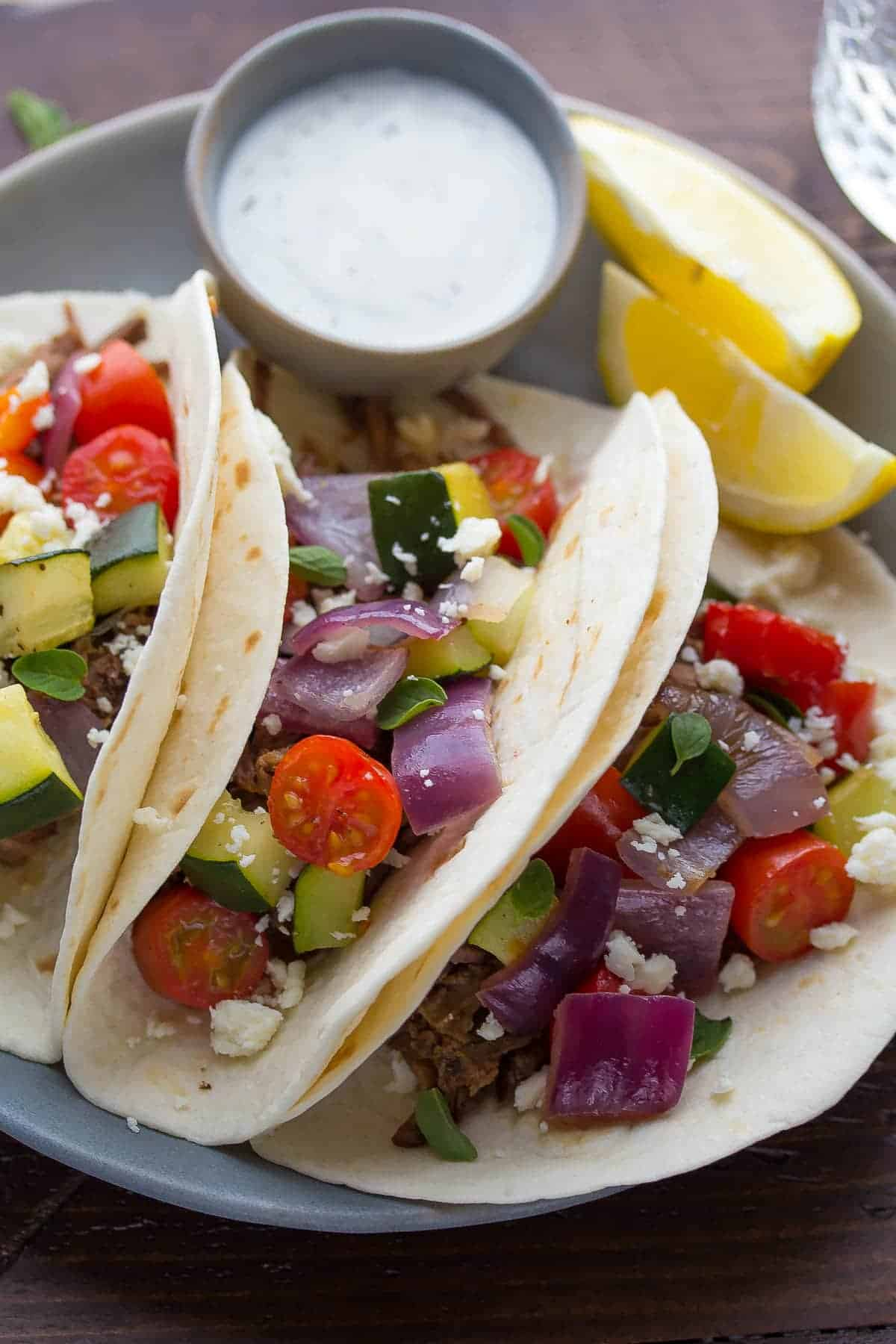 Slow cooker beef tacos with roasted vegetables and feta cheese! Easy to make ahead and best served with tzatziki.