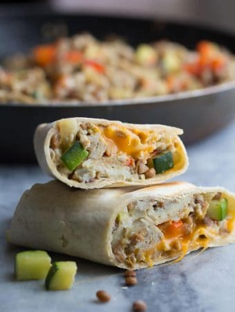 stack of two zucchini lentil breakfast burritos on gray counter