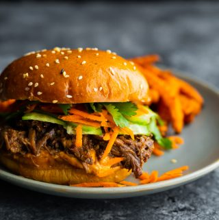 honey garlic shredded beef sandwich on a plate with sweet potato fries