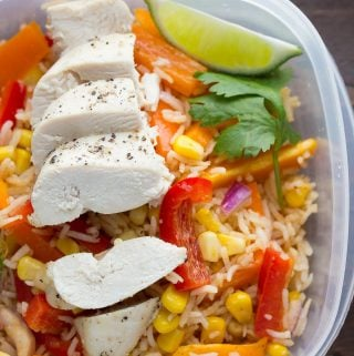 Close up shot of a meal prep container with chicken fajita lunch bowls and lime wedge