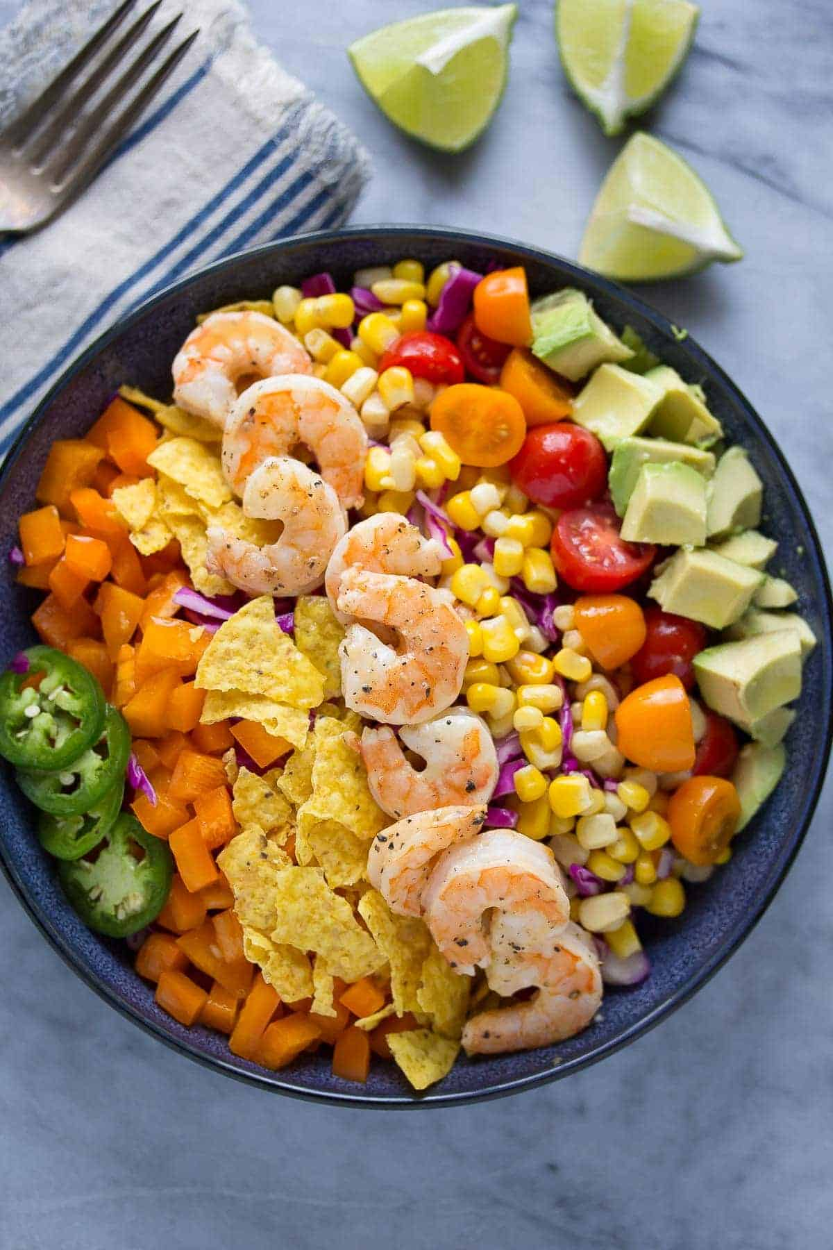 A light and fresh shrimp taco salad recipe that is packed full of veggies and tossed in a honey-lime vinaigrette. Ready in 20 minutes!