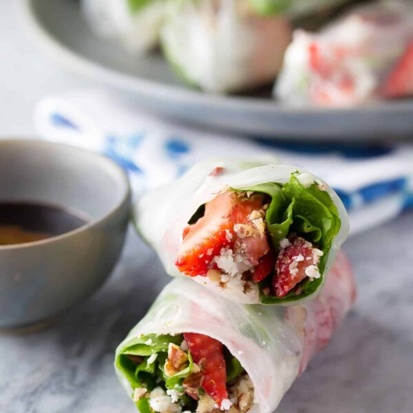 two strawberry spinach salad rolls stacked with dipping sauce