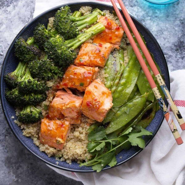 overhead shot of sweet chili salmon broccoli quinoa bowl with chop sticks