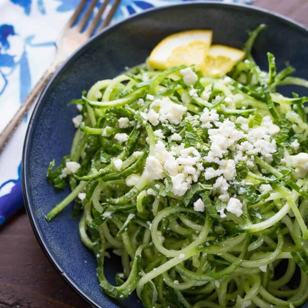 spiralized cucumber feta and mint salad on blue plate with lemon slices