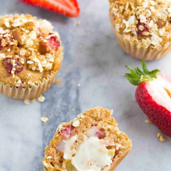 three strawberry apple crumble muffins on gray counter with fresh strawberries