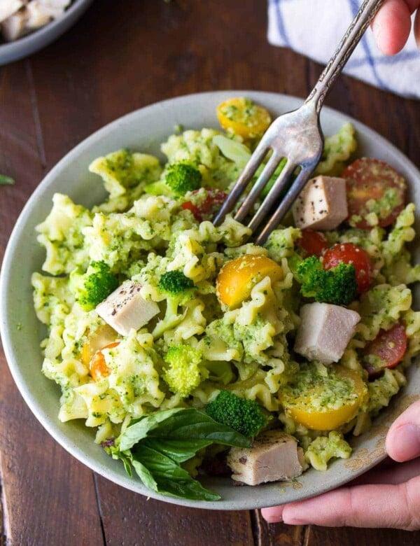 almond broccoli pesto pasta in white bowl with a fork taking a bite
