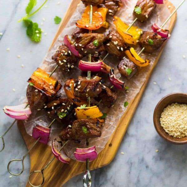 overhead shot of three korean beef skewers on wood cutting board