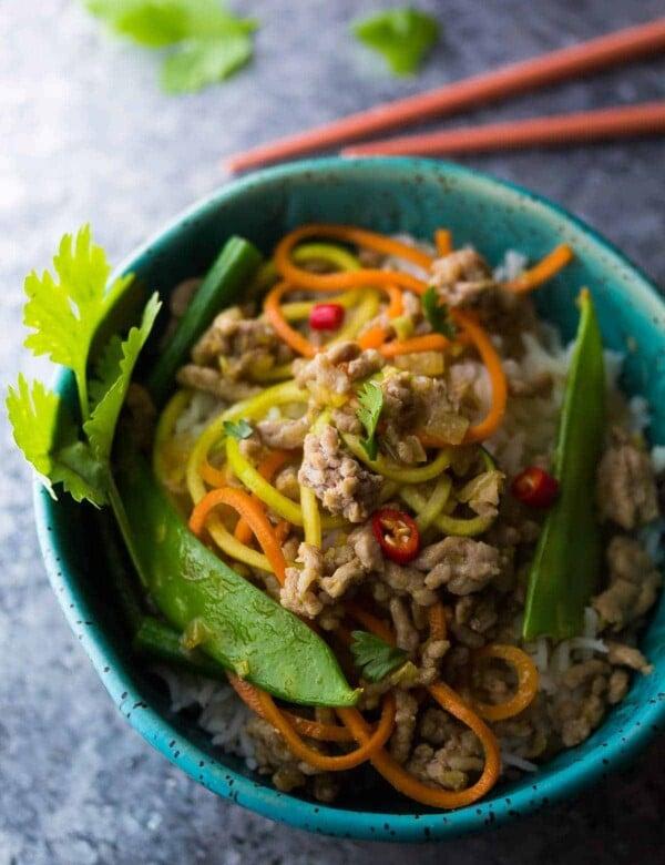 blue bowl with thai ground pork stir fry in blue bowl with chopsticks