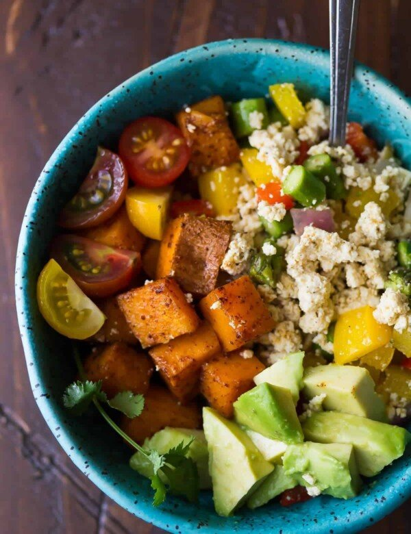 blue bowl filled with tofu breakfast scramble with sweet potatoes and avocado