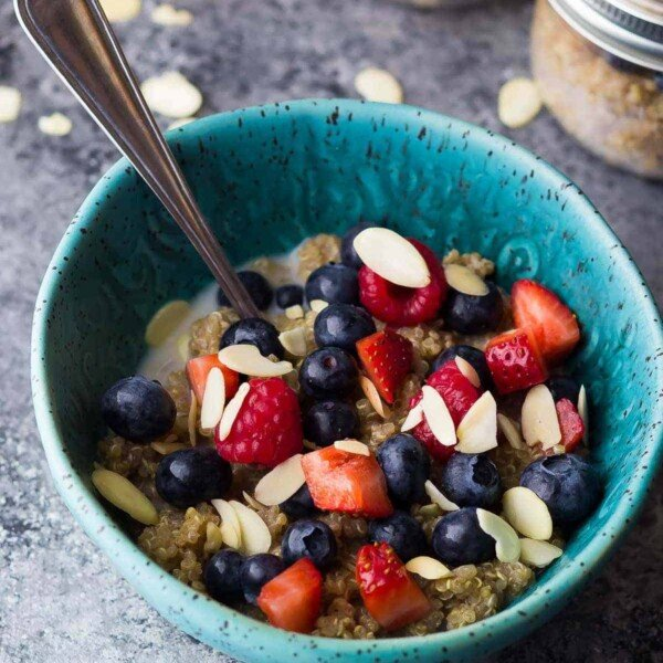 blue bowl with berry almond breakfast quinoa and spoon
