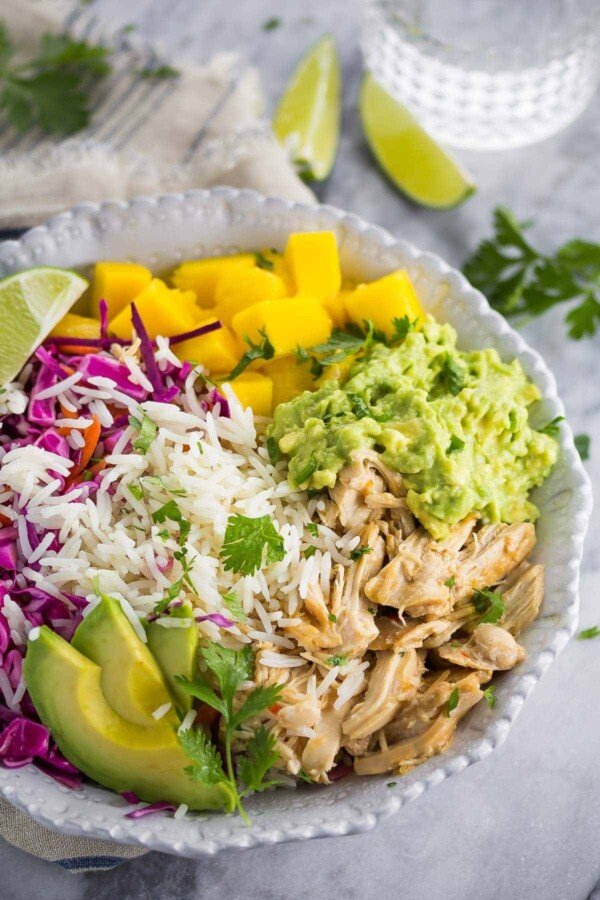 sweet chili chicken bowls with mango and cashews in large white bowl