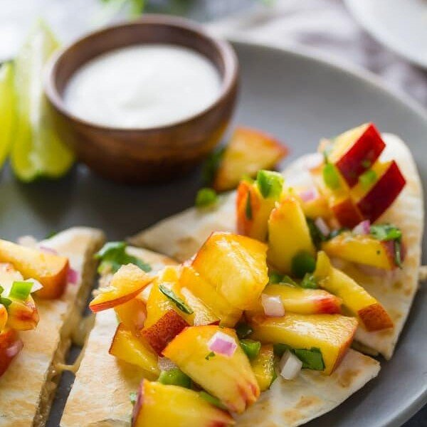 sweet chili chicken quesadillas with peach salsa on gray plate with lime wedge