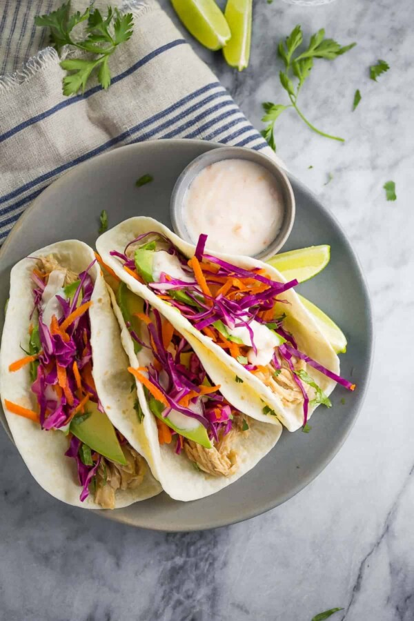 three sweet chili chicken tacos on gray plate with dipping sauce