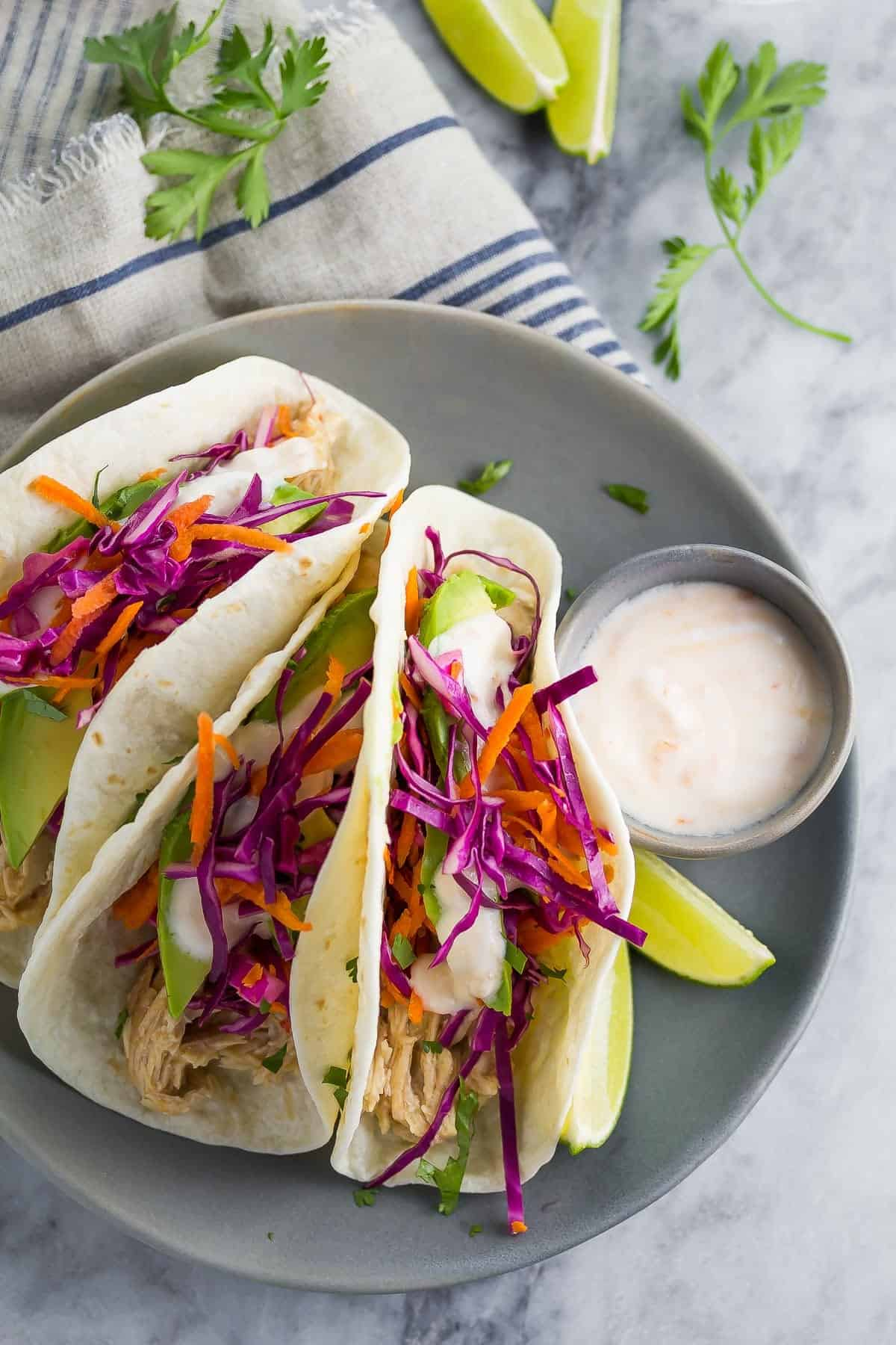 overhead view of Sweet Chili Chicken Tacos plated with slaw and yogurt sauce
