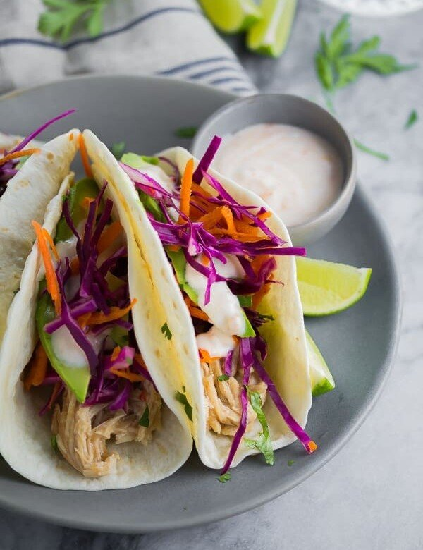 three sweet chili chicken tacos on gray plate with dipping sauce and lime wedges